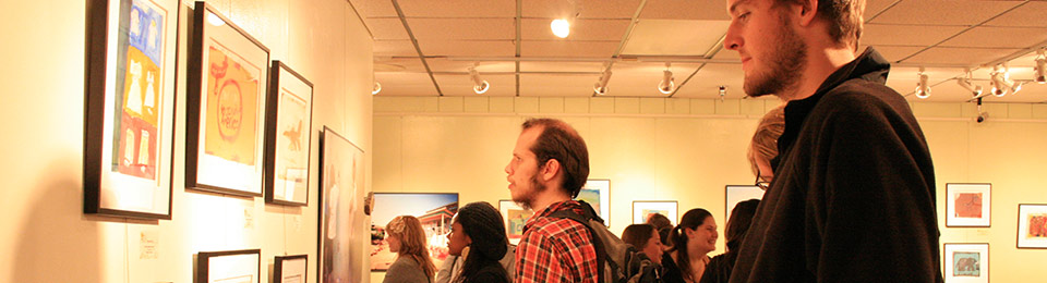 Photo of spectators admiring art displayed in the Oglesby Gallery